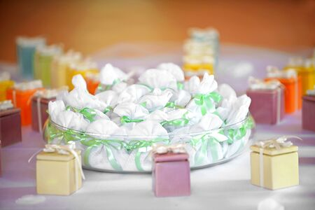 party favors: Assorted party favors displayed on a table with colorful gift boxes tied with bows and a bowl of little bags tied with green ribbon
