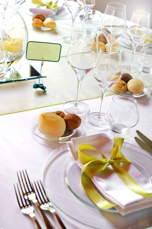 formal place setting: Formal luxury table setting for a catered event with linen, dinnerware and glasses decorated with gold bows and place names, close up view on one place setting
