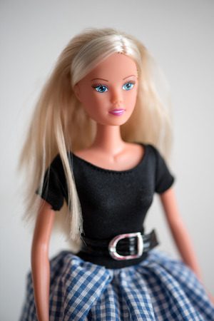 playthings: Single smiling blue eyed doll in black blouse, long blond hair and checkered blue and white skirt Stock Photo