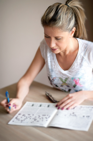 pony tail: Attractive blond woman with a pony tail sitting at a table at home relaxing and doing crossword puzzles