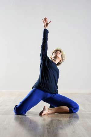 Young woman striking a graceful yoga pose kneeling barefoot on the floor with her arm raised looking upwards as she does her exercises and workout