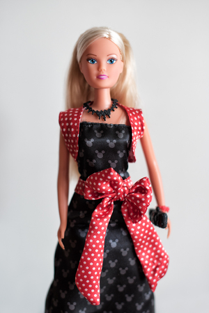 evening wear: doll with long blond hair in evening wear with a red sash carrying a purse isolated on grey