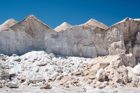 evaporacion: Montículos de sal o solución salina secan por evaporación del calor del sol en una granja de la sal comercial bajo un cielo azul claro y soleado Foto de archivo
