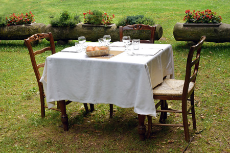al fresco: Wooden tablecloth set with a formal table setting and two chairs for al fresco dining on a private lawn in summer sunshine Stock Photo
