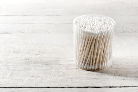aseo: recipiente de plástico cilíndrico de bastoncillos de algodón blancas y limpias en un concepto de cuidado de la salud y la higiene en un tablero de madera blanca con espacio de copia