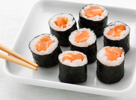 chop sticks: Serving of seven hosomaki salmon sushi at a sushi bar arranged on a plate with chop sticks in a close up high angle view