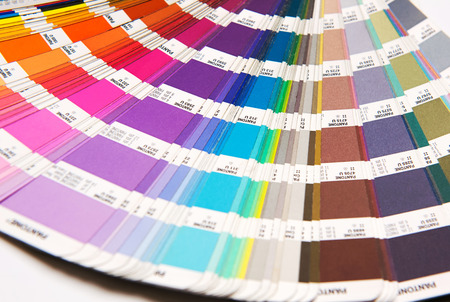 spectral: Opened Pantone color chart fanned out to show the spectrum of color swatches for fashion and interior decoration