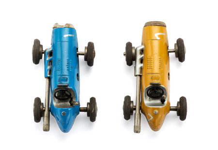 View from the top of two model vintage toy racing cars side by side in yellow and blue isolated on white