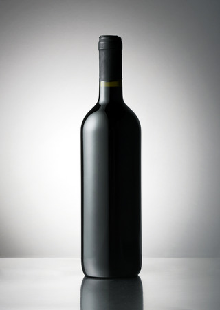 unlabelled: Plain capped red wine bottle with a blank label space for branding or advertising on a reflective table over a grey gradient background