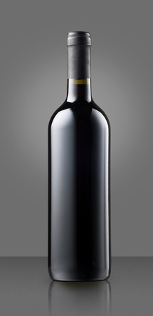 oenology: Blank full capped red wine bottle on grey with copy space for a label or branding for a winery in a concept of oenology, wine making and viticulture Stock Photo