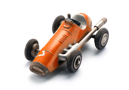 Colorful orange vintage toy racing car in a three quarter front view from above on a white background with copy space Stock Photo