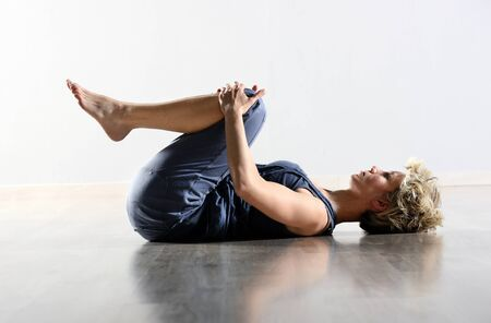 Young woman working out in a gym doing fitness exercises and abdominal crunches, low angle side view in a healthy lifestyle and fitness concept