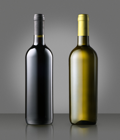 oenology: Unlabelled corked full red and white wine bottles standing side by side on grey conceptual of a winery, wine making, viticulture or oenology
