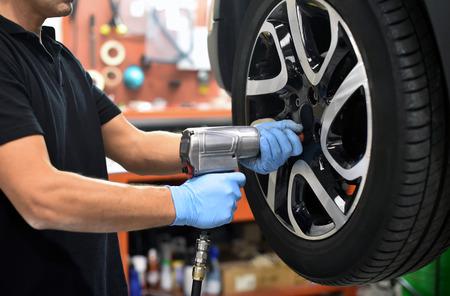 Mecánico que cambia un neumático de coche en un taller en un vehículo en un alzamiento usando un taladro eléctrico para aflojar los pernos en un concepto de servicio o reemplazo Foto de archivo - 67745516