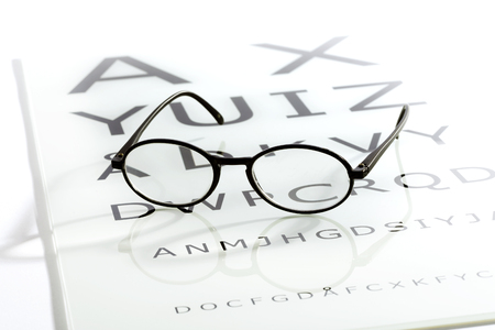 sight chart: Black oval glasses laying over white glossy eye chart table, sight test optometry concept Stock Photo