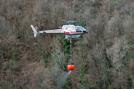 full suspended: Helicopter transporting a bucket full of water suspended below the plane as it fights a mountain fire in the wilderness