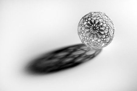 wirework: Single openwork sphere ball casting long shadow isolated on white background