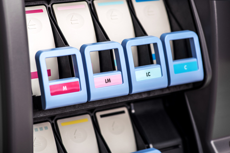 Close-up view of professional wide format printer ink loading mechanism with handles marked up with letters