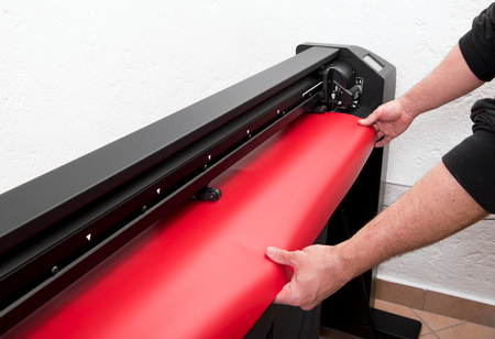 Hands of printing master loading red wide format film on plotter machine, close-up incognito view