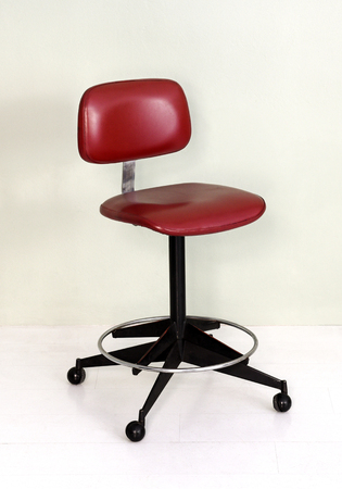 Furniture Still Life of Vintage Office Chair with Red Seat and Wheel Casters in Room with White Background and Floor Stock Photo