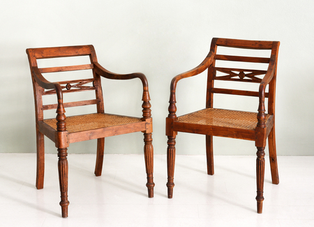 Two vintage colonial style wooden armchairs with spindle form legs and wicker or cane seats, possibly servers from a dining set