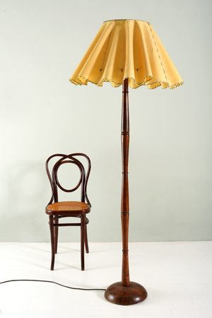 Furniture Still Life of Floor Lamp with Wood Base and Decorative Ruffled Yellow Shade Beside Small Wood Chair in Room with Plain Background and Floor