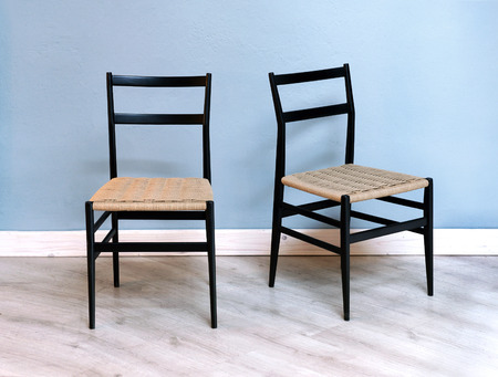 Two Simple Black Kitchen Or Dining Chairs With Woven Wicker Seats Against A  Blue Wall On