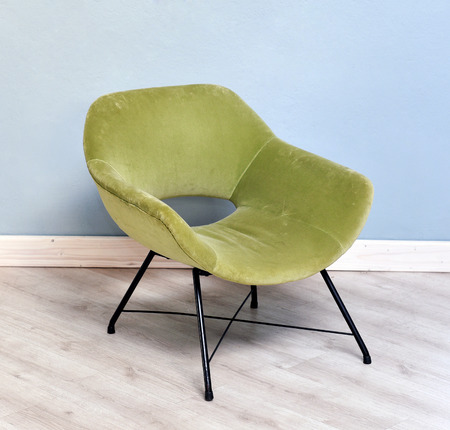 Furniture Still Life of Small Retro Green Velvet Plush Reclining Chair with Black Metal Legs in Room with Wood Floor and Light Blue Wall