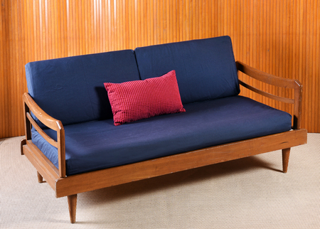 High Angle Still Life View Of Vintage Wood Sofa With Navy Blue And Red  Cushions In