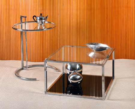 Furniture Still Life of Glass and Chrome Side Table and Coffee Table with Silver Tea Pot, Bowl and Decorative Globes in Room with Beige Carpet and Wall Wood Paneling