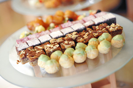 Assorted sweets and bonbons displayed in a store on a flat round reflective surface in a close up view