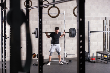 Man lifting heavy barbell on squat rack, gym equipment in foreground