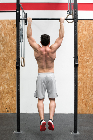 Rear view of muscular bare chested man hanging from rings in gym