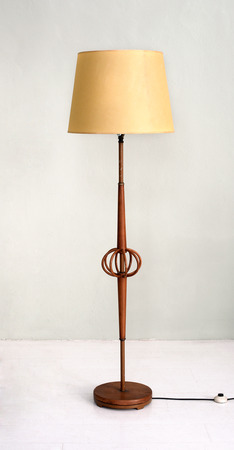 Stylish wooden electric floor lamp with yellow shade and open bentwood centrepiece in an interior decor concept
