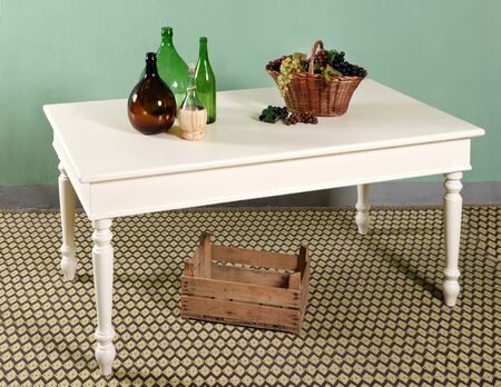 White vintage kitchen table decor still life composition of empty bottles and wicker basket of grapes and empty wooden box on carpet floor under the table Stock Photo