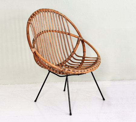 Comfortable round wicker chair with metal legs made with intertwined willow canes in an interior decor and design concept