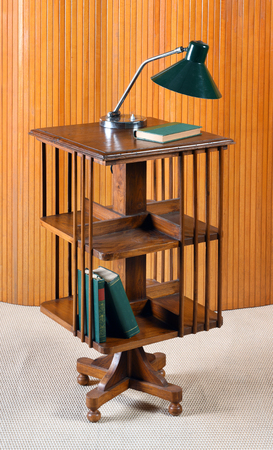 Small stylish mobile wooden bookcase on casters with a vintage lamp on top and books on the shelves in an interior design concept