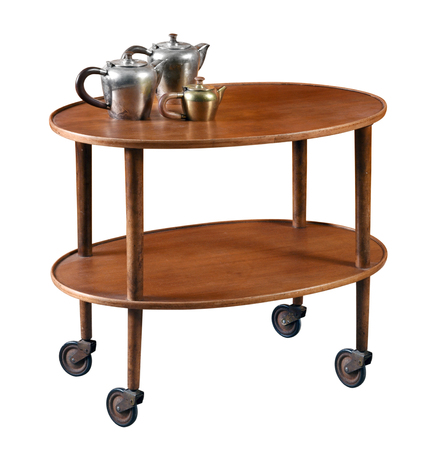 Oval mahogany serving cart on wheels with a single lower shelf and an old vintage metal tea set on top isolated on white