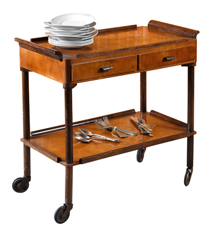 Vintage rectangular wooden serving trolley with a top gallery, two drawers and lower shelf on wheels with a stack of clean plates on top and assorted cutlery below isolated on white