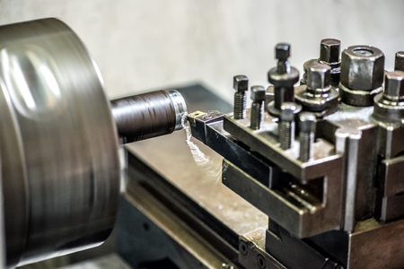 clamped: Close-up of lathe machine working with pipe clamped inside the chuck and cutter removing thin layer of metal