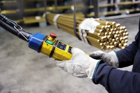 Close-up of worker hands in gloves manipulating indoor overhead crane on factory pushing buttons on pendant control to lift up metal pipes blurred in background Imagens