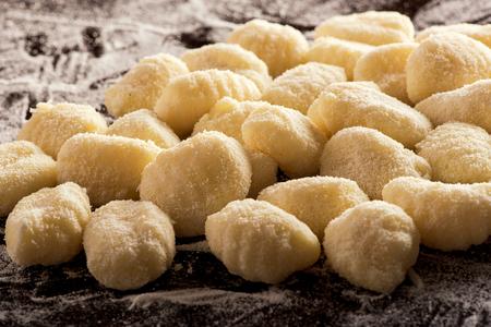 Pile of uncooked Italian semolina dumplings on rustic background