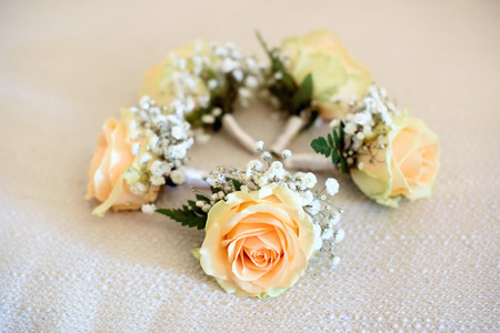 Close-up of five wedding corsages accessory made from peach rose located in circle on white cloth surface