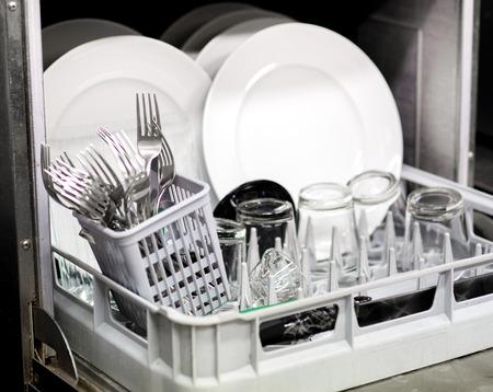 Maak generieke witte gerechten, glazen en bestek schoon in een vaatwasser, van dichtbij bekeken door de open deur