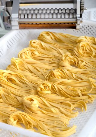 Freshly made Italian fettuccine pasta on a white plastic tray in a restaurant ready to be used as an ingredient for cooking in a close up view Stock Photo