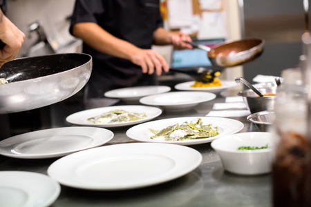 plating: Restaurant kitchen with chefs preparing a meal serving food onto white plates from saucepans in a low angle close up view