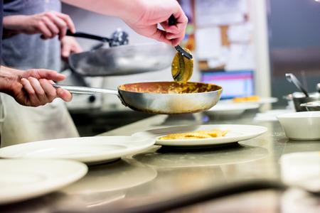 Chef-kok die deegwaren in een Italiaanse restaurantkeuken dient die het van de pan op een witte plaat in een dichte omhooggaande mening van zijn handen lepelt Stockfoto