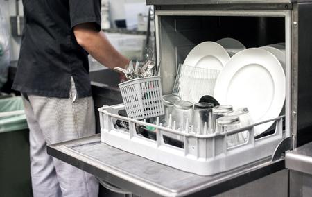 케이터링 및 위생 개념 레스토랑 주방에서 깨끗한 흰색 번호판으로 가득 찬 식기 세척기와 주방 손 스톡 콘텐츠