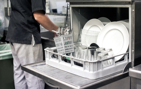 Kitchen hand with an open dishwasher filled with clean white plates in a restaurant kitchen in a catering and hygiene concept Stockfoto
