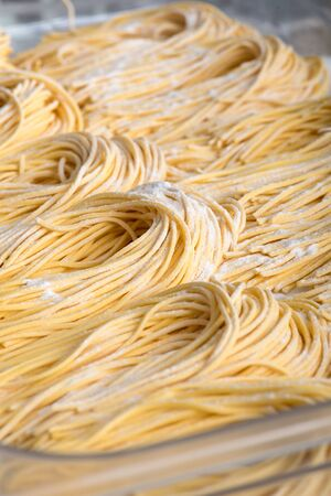 Close up of freshly made Italian spaghetti pasta on a tray in a restaurant kitchen arranged in individual piles ready for cooking for clients meals